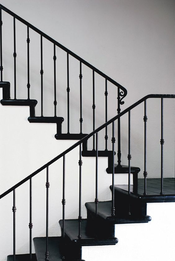 black and white space with a stylish staircase with black iron handrail and balustrade
