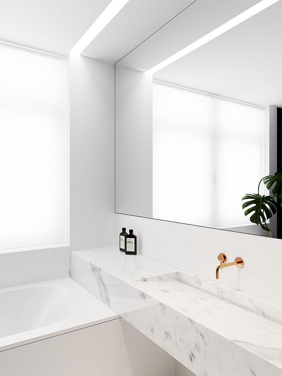 small white marble modern bathroom with a mirror and counter in a niche
