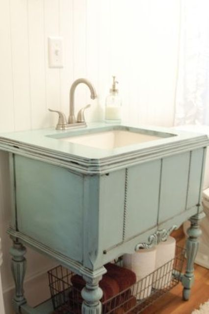 repurposed sewing machine cabinet was painted patina color and used as a vanity
