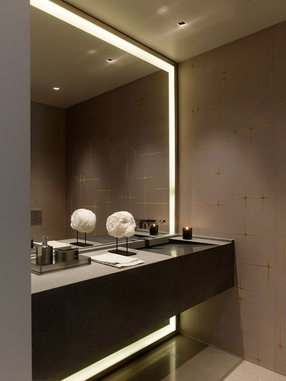 dark glam bathroom with a lit up mirror in a niche