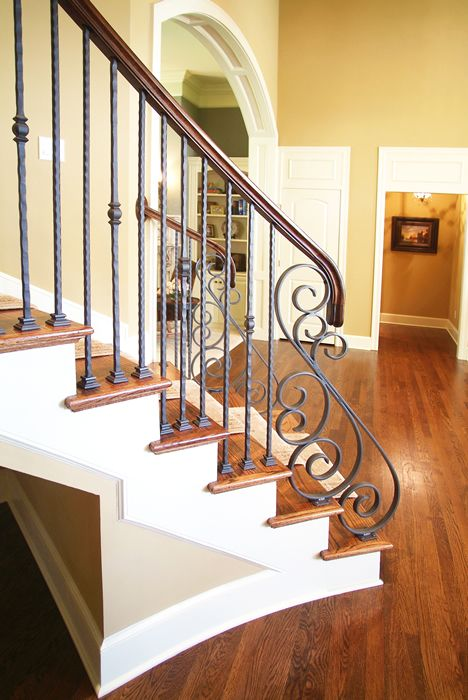warm wood staircase and wrought iron balustrade of a lighter color to stand out