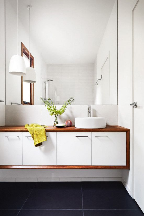a niche with a floating mid century modern vanity and a mirror