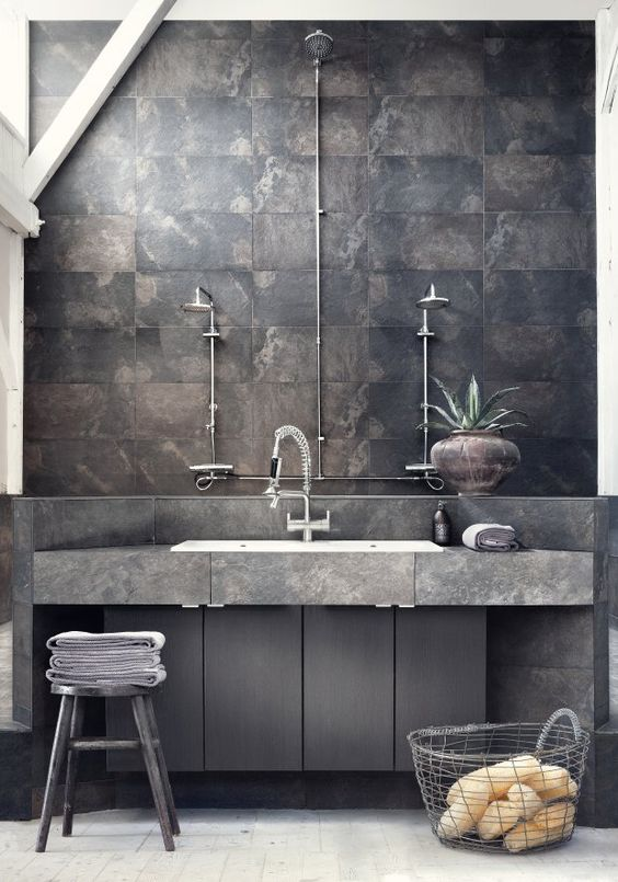 a stone vanity with wooden cabinets underneath for a masculine bathroom