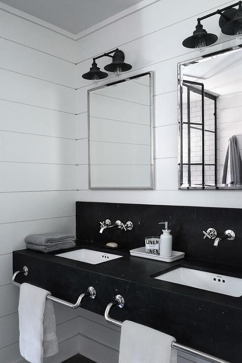 black and white industrial bathroom features a honed black marble floating dual vanity accented with built in polished nickel towel bars and square undermount sinks