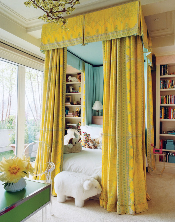 bold canopy bed in a kid's room with sunny yellow curtains