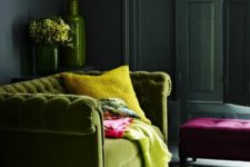 35 green plush sofa and bold yellow accents in a moody room