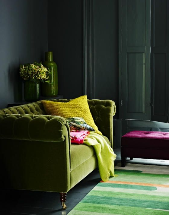 green plush sofa and bold yellow accents in a moody room