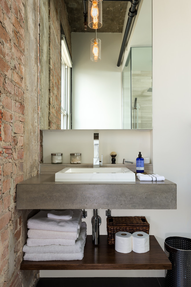 A minimalist concrete vanity looks great by an exposed brick wall. (CONTENT Architecture)