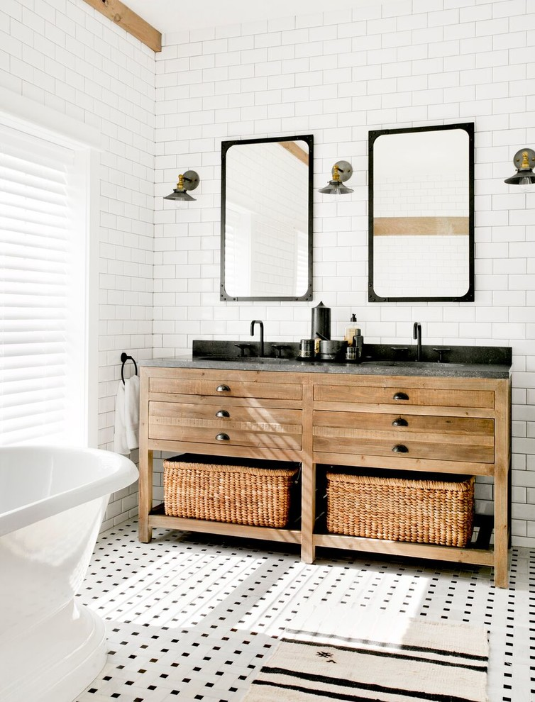 Black countertop looks great on a wooden vanity with lots of drawers and storage baskets. (Timothy Godbold Ltd)