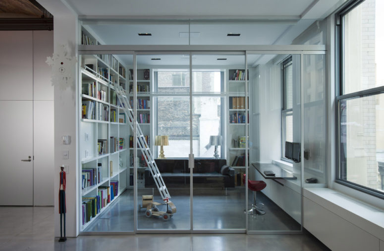 an enclosed home office/library behind a glass wall with sliding doors