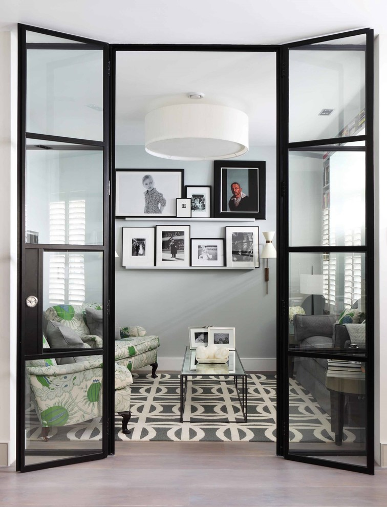 an enclosed living room with a gallery wall hides behind floor to ceiling french doors