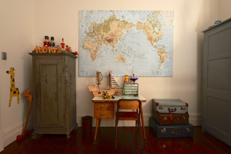 This is how you could rock both, a stack of vintage suitcases and a world map in a kids room (Jeni Lee)
