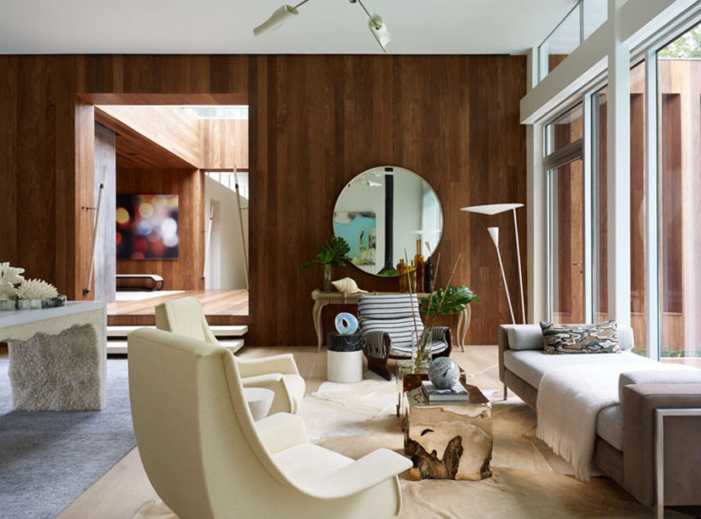 A warm-colored wood wall is a partition, and a glazed one connects the living room with outdoors