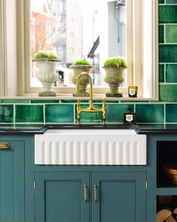 The blue cabinets with copepr handles look elegant and traditional, and stone urns are used instead of usual pots