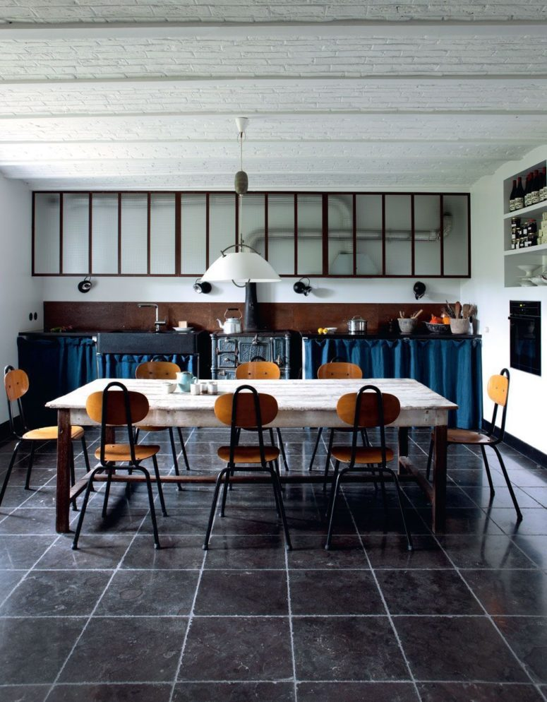 The kitchen is vintage and industrial, with curtains instead of doors and an antique metal hearth