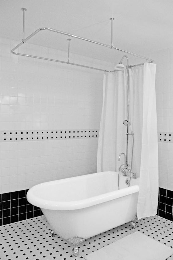 a classic clawfoot tub and shower in a timeless black and white bathroom