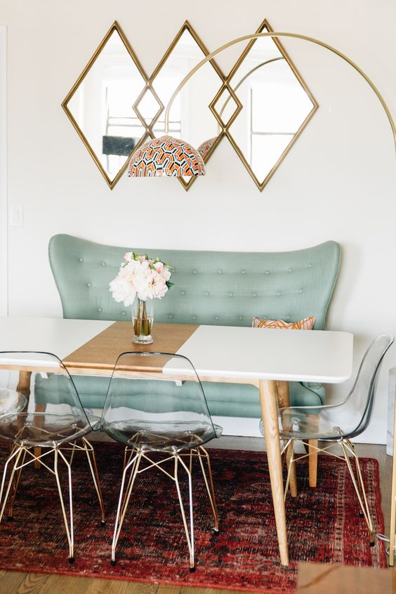 a color blocked dining table in black and copper with wooden legs looks cute with acrylic chairs and a mint love seat
