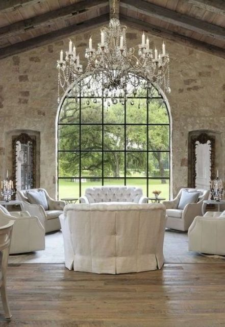 a vintage living room with white fabric furniture and an oversized vintage chandelier with hanging crystals, candles and bead garlands