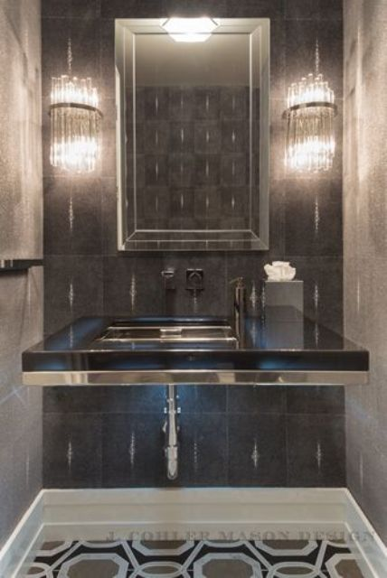 chic sleek black sink stand with a metallic sink and an echoing mirror frame