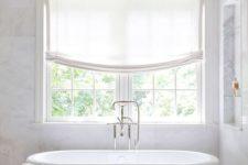 02 refined modern bathtub with a silver stool, Roman shades and a freestanding bathtub