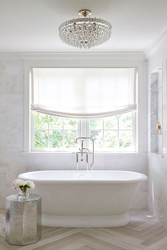 refined modern bathtub with a silver stool, Roman shades and a freestanding bathtub
