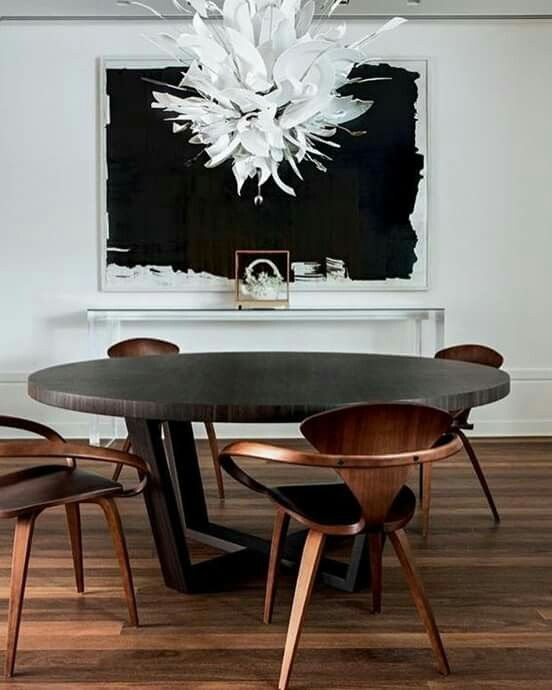 this round dark dining table makes a bold statement and everything is centered around it