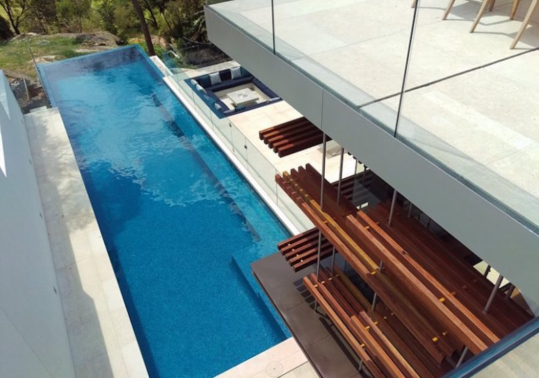 A long, rectangular swimming pool extends and cantilevers over the edge of the slope