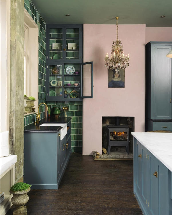 An antique metal hearth looks creative with a pink wall, and a vintage portrait adds a glam feel