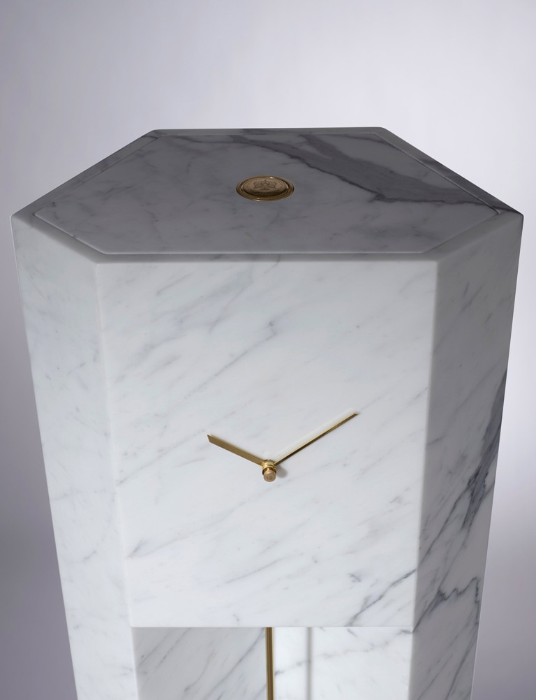 It also contains a traditional clock mechanism, which was modified by the designer to use one central weight