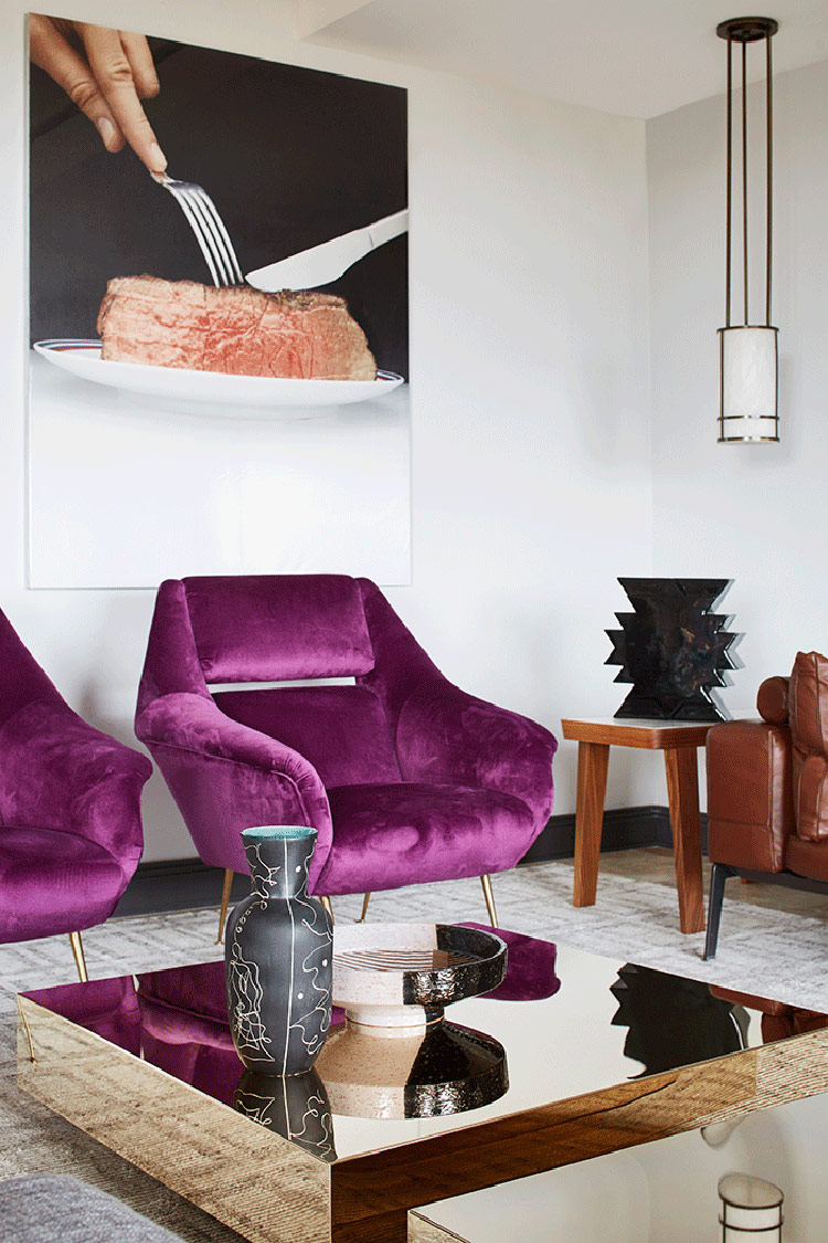 Purple upholstered chairs, gold mirror tables and creative oversized photos on the wall make the space unique
