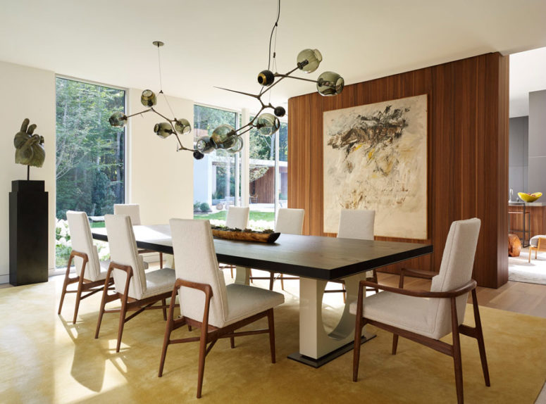 The dining space is a comfy one with upholstered chairs and a stunning dark glass chandelier