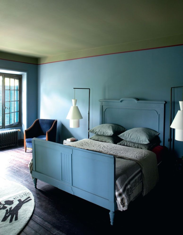 The master bedroom is done in blue shades, it features cool architectural lamps and a cobalt blue chair