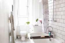 03 a narrow bathroom with a white clawfoot tub and patterned floor tiles