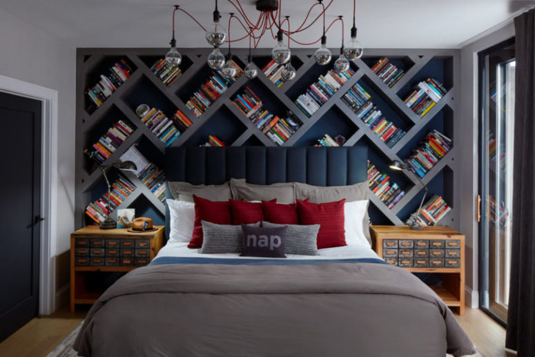 The bedroom features a large herringbone bookshelf, a cool industrial chandelier with red cords and apthecary chest inspired bedside tables