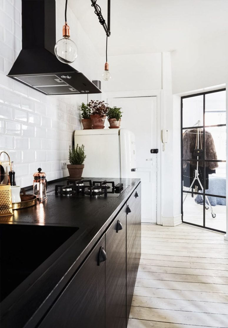 The kitchen features black cabinets, industrial bulbs over them and a white tile backsplash