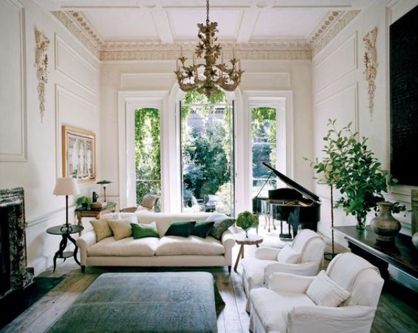 The living room is gorgeous with large windows, stucco and comfy modern furniture, a vintage piano and a cool fireplace create a refined feel