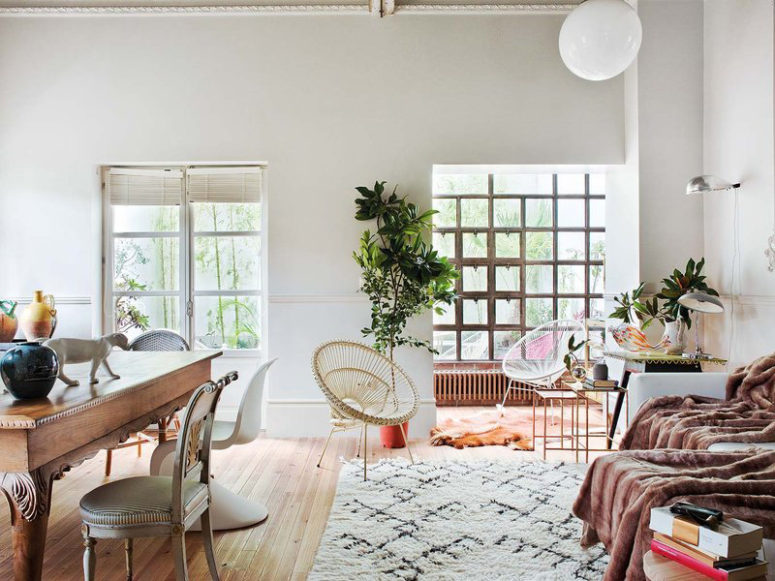 The living room is united with the dining space and this open layout is flooded with light