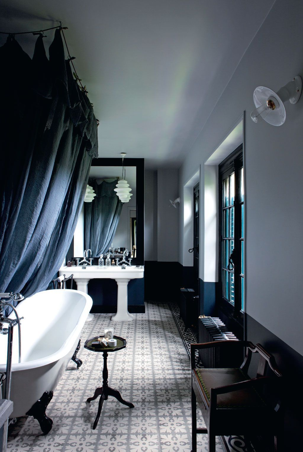 The master bathroom is refined, with teal, black and white and vintage sinks and a bathtub