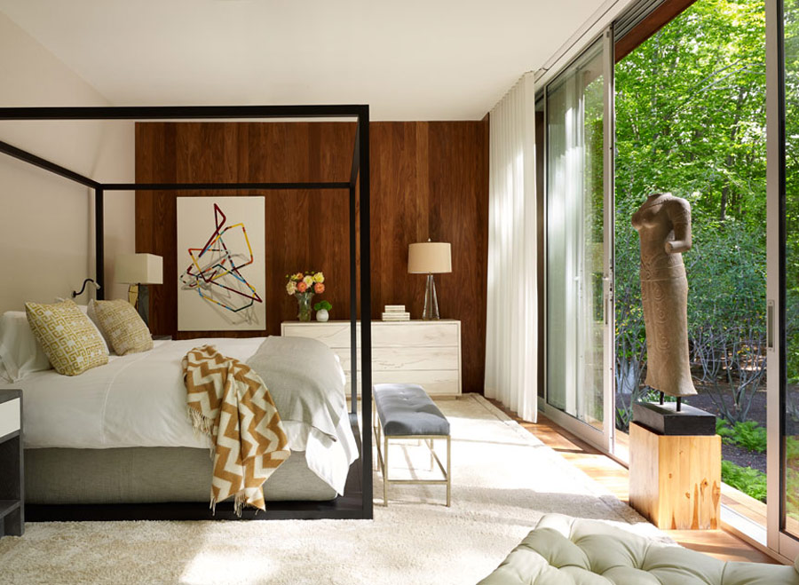 The master bedroom features a large framed bed, a geometric wall art and an antique sculpture