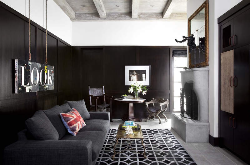 There's a dark room done in black, with a fireplace and an oversized mirror, for a contrast and a soothing ambience