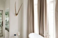 04 a feminine space with beige curtains, a pink stool and a refined oval bathtub on nickel legs