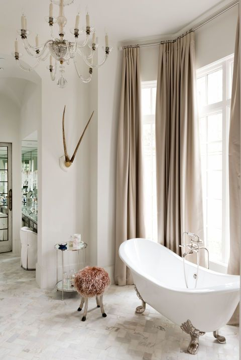a feminine space with beige curtains, a pink stool and a refined oval bathtub on nickel legs