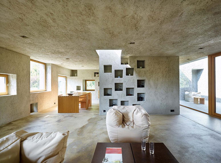 Concrete also dominates the interiors, it covers walls, floors and ceilings, and light-colored wood makes them cozier