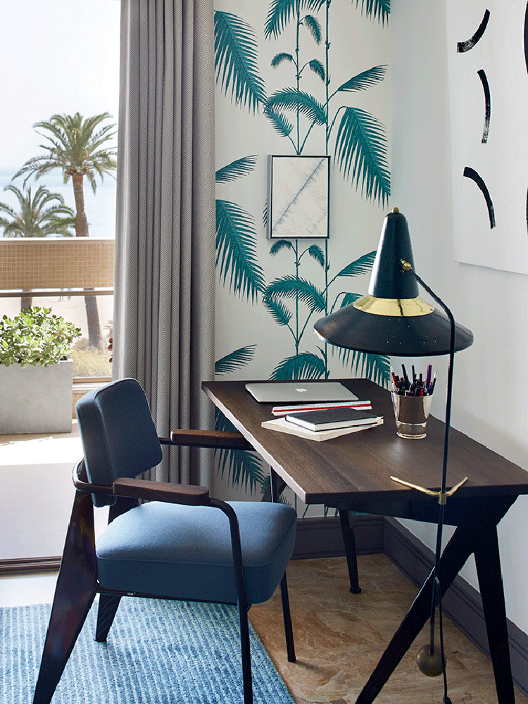 The home office nook features botanical print wallpaper and a withc hat inspired floor lamp