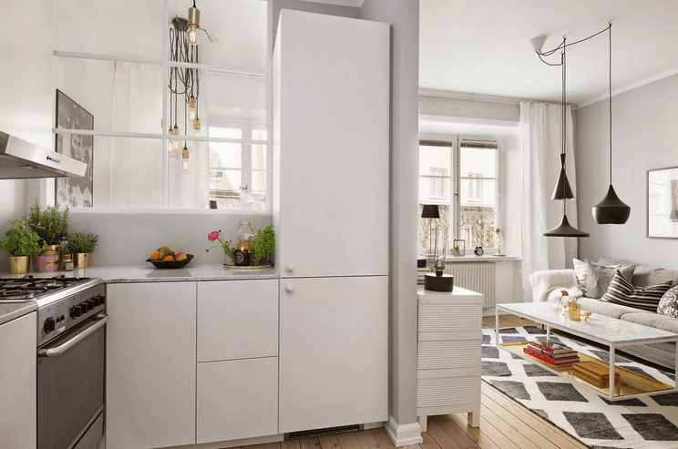 The kitchen is white with metallic accents and a false window going to the bedroom