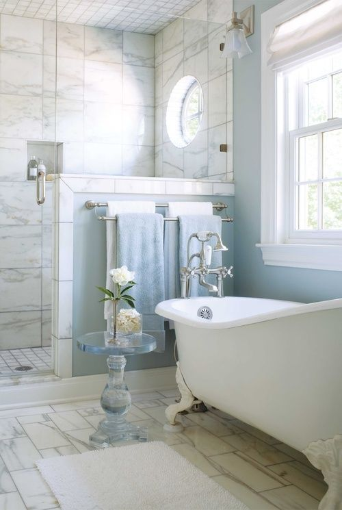 a light blue bathroom with a slip clawfoot tub with white legs
