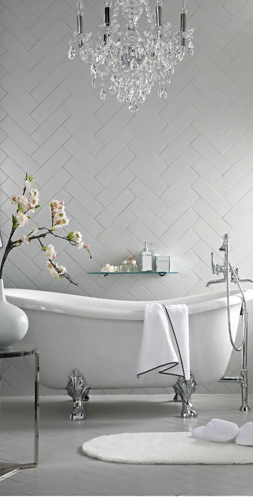 a modern chic bathroom with a clawfoot tub, herringbone tiles and a gorgeous crystal and silver chandlier