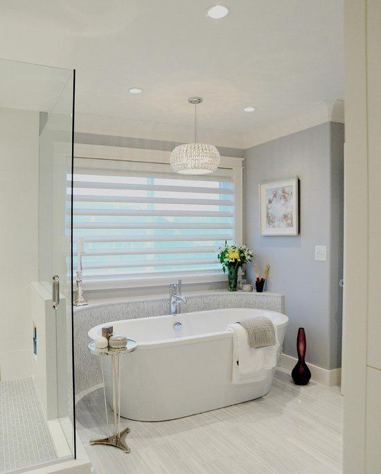 a modern freestanding bathtub in an alcove, a glam crystal chandelier and a metal stand