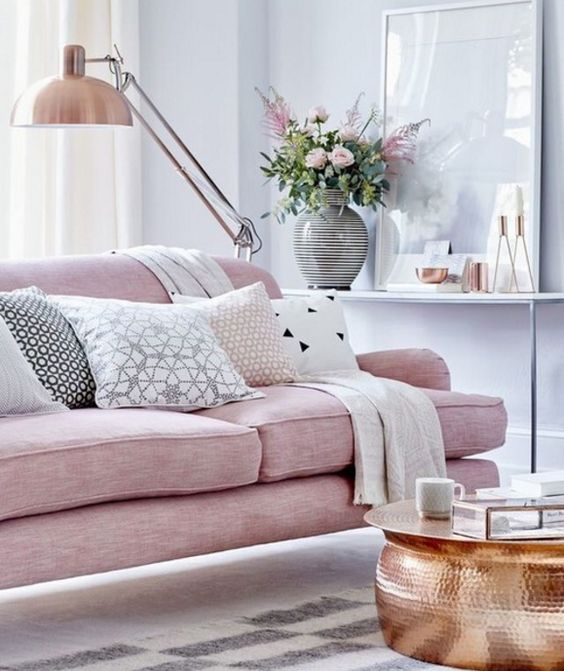 a pink upholstered sofa on tall legs looks cool with copper details
