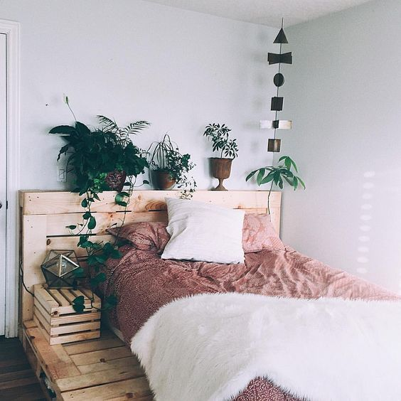 a rustic bed made of pallets can be made more feminine with pink bedding and faux fur